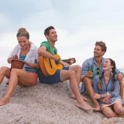 Menschen am Strand singen
